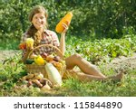 Gardener girl with basket of harvest in garden - stock photo