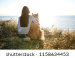 Stock photo young beautiful woman with long hair walking with collie dog outdoors in the park near the sea 1158634453