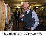 winemakers in wine cellar... | Shutterstock . vector #1159028440