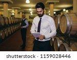 winemakers in wine cellar... | Shutterstock . vector #1159028446