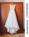 Stock photo beautiful a line wedding dress with floral embroidery is hanging in the morning of a wedding day 1159048390
