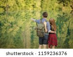 Small photo of young amorous man is standing with his girlfriend and pointing at the magnificent nature. back view photo.holiday, day off concept. copy space