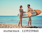 smiling young couple of surfers ... | Shutterstock . vector #1159259860