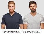 Two bearded brothers in casual t shirts, have serious expressions, stand next to each other, isolated over white background. Handsome ginger hipster guy and his companion think about something