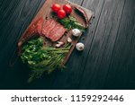 smoked salami on a black table... | Shutterstock . vector #1159292446