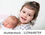 little sister hugging her...   Shutterstock . vector #1159648759