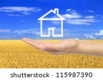 Virtual house with woman hand on wheat field background - stock photo