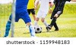 children kicking football ball... | Shutterstock . vector #1159948183