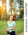 joyful young woman jogging... | Shutterstock . vector #1160167489