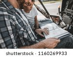 Small photo of Happy bearded male and concentrated kid discussing their letdown while looking at map. They sitting in cozy cabin of helicopter