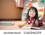 Small photo of A cute little child Asian girl doing homework and reading a book. Kid enjoy learning with happiness at home. Clever,Education and smart learning concept