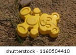 Small photo of forgotten children's toy on the sand, yellow,bear.