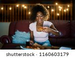 woman eating pizza and watching ... | Shutterstock . vector #1160603179