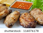 Grilled chicken wings with hot pepper sauce and chips - stock photo