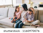 mother is sitting on sofa with... | Shutterstock . vector #1160970076