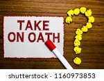 Small photo of Text sign showing Take On Oath. Conceptual photo A solemn appeal to a deity Speak the truth Make a Promise White paper marker crumpled papers forming question mark wooden background.