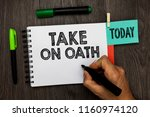 Small photo of Conceptual hand writing showing Take On Oath. Business photo showcasing A solemn appeal to a deity Speak the truth Make a Promise Man holding marker notebook reminder cup markers wood table.