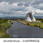 Small photo of Falkirk, United Kingdom - August 09 2018: Tourists around the Kelpies - a pair of large horse head statues made from Stainless steel by Sculptor Andy Scott, along side the Forth and Clyde canal