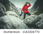 Caucasian Professional Nature Photographer in His 30s with Digital Camera in Front of the Glacier Preparing For the Shot. Photography Contract Theme.  - stock photo