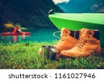 Waterfront Kayak Camping Concept Photo. Kayak and Trail Shoes on the Shore and the Kayaker on the Glacial Lake Water in the Background.  - stock photo
