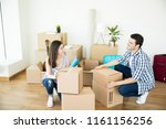 Small photo of Happy mid adult man and woman in casuals crouching while stacking cardboard boxes in new home