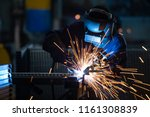 Workers wearing industrial uniforms and Welded Iron Mask at Steel welding plants, industrial safety first concept. - stock photo