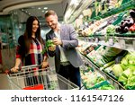young couple buying vegetables... | Shutterstock . vector #1161547126