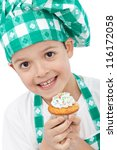 Happy child with chef hat holding muffin - closeup - stock photo