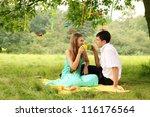 Young couple drinking tea in the park - stock photo
