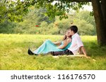 young couple sitting under a tree hugging - stock photo