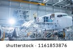 Small photo of Engineer in Safety Vest Standing next to Airplane in Hangar