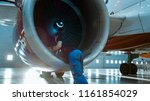 Stock photo in a hangar aircraft maintenance engineer technician mechanic inspects with a flashlight airplane 1161854029