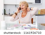 confused senior woman sitting... | Shutterstock . vector #1161926710