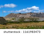 Small photo of dumps of mined rock with spreader and working bulldozer, general view