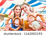 two friends wearing dirndl are... | Shutterstock . vector #1162002193