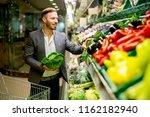 young man buying vegetables in... | Shutterstock . vector #1162182940