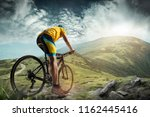 The young fit man in helmet conquering mountains on a bicycle. The bike, nature, bicycle, sport, cycle, extreme, lifestyle, adventure and sport concept - stock photo