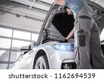Modern Certified Car Service. Caucasian Mechanic in His 30s Checking Crucial Elements of the Engine During Scheduled Warranty Maintenance. - stock photo