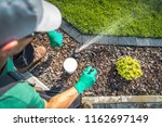 Adjusting Lawn Sprinkler by Professional Garden Irrigation Technician. Top View. - stock photo