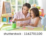 mother with little daughter... | Shutterstock . vector #1162701100