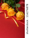 Yellow roses on red satin with space for text - stock photo