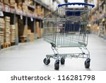 Shopping trolley cart before Rows of shelves with storage boxes in huge warehouse - stock photo