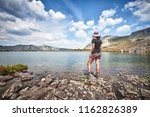 a young woman hiking next to a high alpine lake in the mountains of Colorado - stock photo