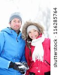 Couple in winter portrait. Young interracial couple smiling looking at camera outside in snow winter forest. - stock photo