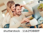 cheerful young couple using... | Shutterstock . vector #1162938889