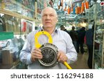 mature man holds  engine clutch  in  auto parts store - stock photo