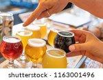 female hand picking up glass of ... | Shutterstock . vector #1163001496