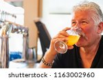 handsome man tasting a glass of ... | Shutterstock . vector #1163002960