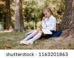 a schoolgirl does lessons in a... | Shutterstock . vector #1163201863