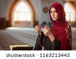 young muslim woman praying in...   Shutterstock . vector #1163213443